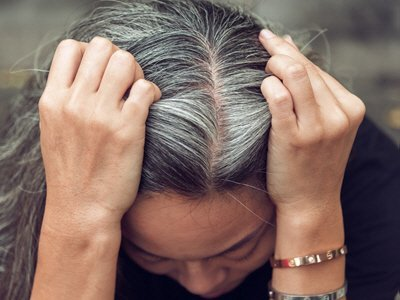 Stressed grey-haired woman holding her hair as she looks down