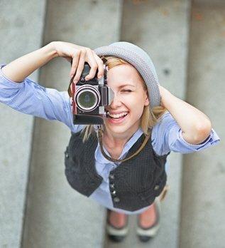 Young lady with camera as she looks upwards towards camera