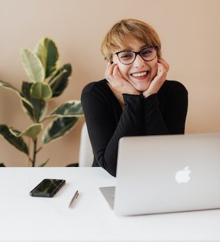 Woman smiling in front of laptop