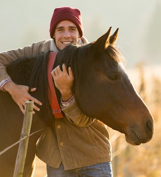 HSP man smiling and holding horse